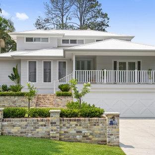 На фото: трехэтажный, белый частный загородный дом в современном стиле с вальмовой крышей, металлической крышей, белой крышей и отделкой планкеном