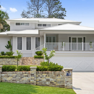 Exempel på ett modernt vitt hus, med tre eller fler plan, valmat tak och tak i metall