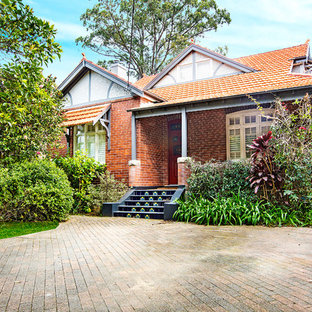 Inspiration for a traditional two-storey brick red house exterior in Sydney with a gable roof and a tile roof.