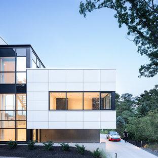 Foto de fachada de casa blanca, moderna, a niveles, con revestimiento de aglomerado de cemento y tejado plano