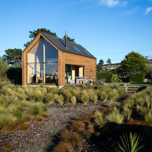 Inspiration for a small coastal one floor house exterior in Dunedin with wood cladding and a pitched roof.