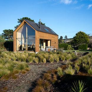Ejemplo de fachada marinera, pequeña, de una planta, con revestimiento de madera y tejado a dos aguas