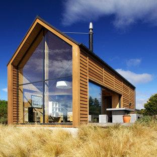 Modelo de fachada marrón, contemporánea, pequeña, de dos plantas, con revestimiento de madera, tejado a dos aguas y tejado de metal