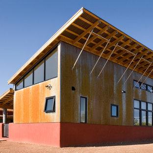 Imagen de fachada roja, industrial, de tamaño medio, a niveles, con revestimientos combinados