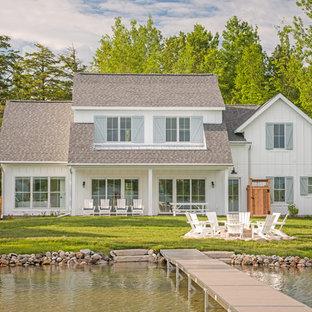 Ispirazione per la villa bianca country a due piani con rivestimento in vinile, tetto a capanna e copertura a scandole