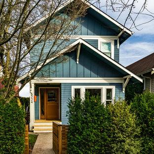 Ispirazione per la facciata di una casa unifamiliare blu american style a due piani di medie dimensioni con rivestimento con lastre in cemento, tetto a capanna e copertura a scandole