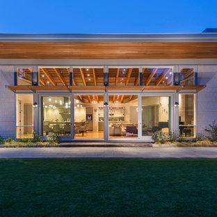Идея дизайна: большой, деревянный, серый частный загородный дом в современном стиле с односкатной крышей