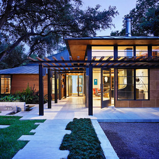 Inspiration for a large zen brown two-story wood exterior home remodel in Austin with a hip roof and a metal roof