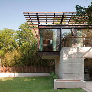 Medium sized and gey modern two floor concrete detached house in Austin with a flat roof.