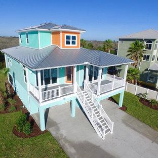Modelo de fachada de casa naranja, marinera, de tres plantas, con revestimiento de aglomerado de cemento, tejado a cuatro aguas y tejado de metal