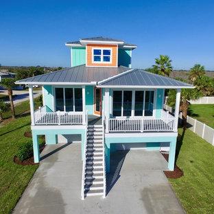 Imagen de fachada de casa naranja, marinera, de tres plantas, con revestimiento de aglomerado de cemento, tejado a cuatro aguas y tejado de metal