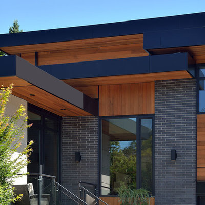 Large contemporary gray two-story mixed siding flat roof idea in Toronto
