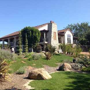 Mediterranean beige two-story stone gable roof idea in San Diego