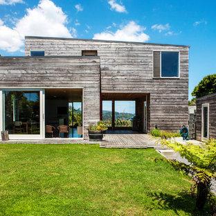 Пример оригинального дизайна интерьера: двухэтажный фасад дома серого цвета в стиле рустика с облицовкой из дерева и односкатной крышей