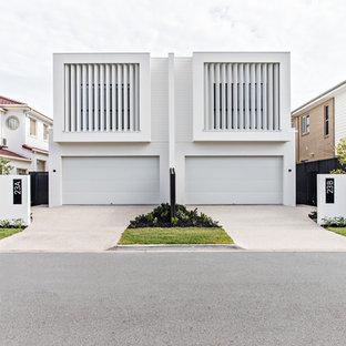 Foto della facciata di una casa bifamiliare bianca contemporanea a due piani con tetto piano
