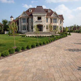 Elegant beige two-story stone exterior home photo in New York with a hip roof and a shingle roof