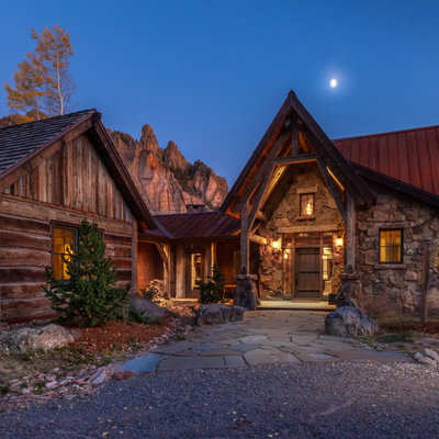 Large mountain style brown one-story mixed siding exterior home photo in Denver with a metal roof and a red roof