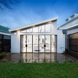 Contemporary one-storey white house exterior in Melbourne with vinyl siding and a shed roof.