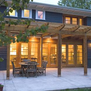 Cette image montre une façade de maison bleue design de taille moyenne et à un étage avec un toit plat et un toit végétal.