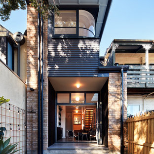 Inspiration for a small contemporary two-storey brick red house exterior in Sydney with a flat roof.