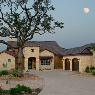 This is an example of a mediterranean exterior in Austin with mixed cladding and a tiled roof.