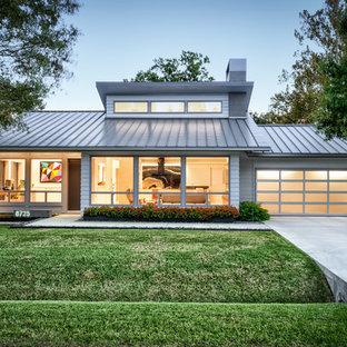 Imagen de fachada de casa gris, vintage, de una planta, con revestimiento de aglomerado de cemento, tejado a cuatro aguas y tejado de metal