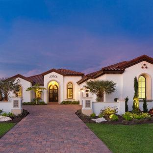 Diseño de fachada de casa blanca, mediterránea, extra grande, de una planta, con revestimiento de estuco, tejado a cuatro aguas y tejado de teja de barro