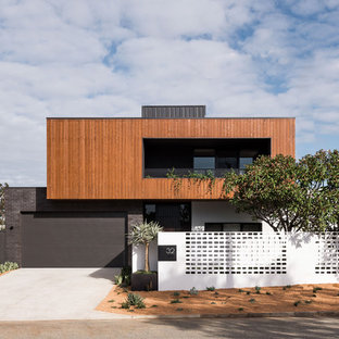 Inspiration for a contemporary two-storey brown exterior in Perth with mixed siding and a flat roof.