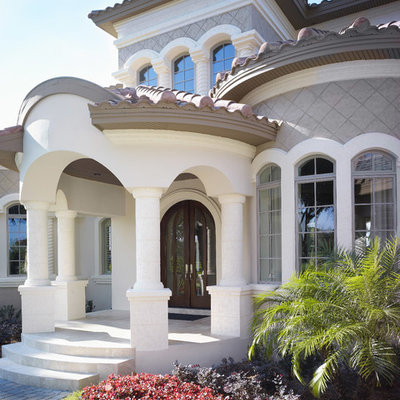 Inspiration for a large mediterranean gray two-story stucco house exterior remodel in Tampa with a hip roof and a tile roof