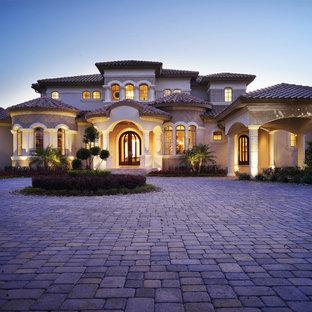 Стильный дизайн: двухэтажный, огромный фасад частного дома бежевого цвета в средиземноморском стиле с вальмовой крышей, облицовкой из цементной штукатурки и черепичной крышей - последний тренд