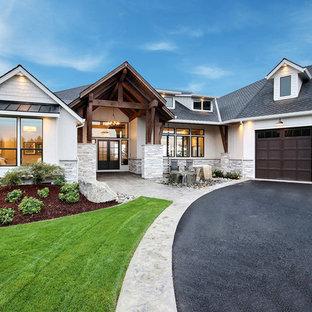 На фото: огромный, белый, двухэтажный частный загородный дом в стиле кантри с комбинированной облицовкой, двускатной крышей и крышей из гибкой черепицы