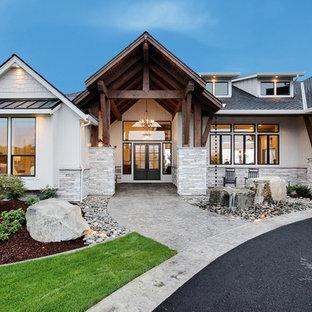 Imagen de fachada de casa blanca, de estilo de casa de campo, extra grande, de dos plantas, con revestimientos combinados, tejado a dos aguas y tejado de teja de madera