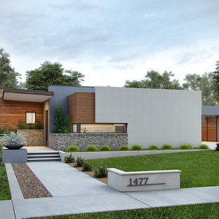 Example of a mid-sized minimalist gray one-story stucco flat roof design in Boise