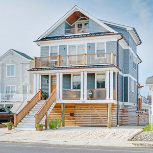 Beach style gray three-story exterior home idea in Other with a metal roof
