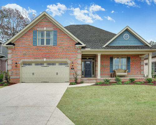 Example of a classic red two story brick exterior home design in other with a