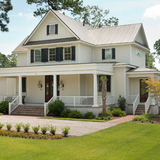 Inspiration for a mid-sized timeless beige two-story wood exterior home remodel in Charleston with a metal roof