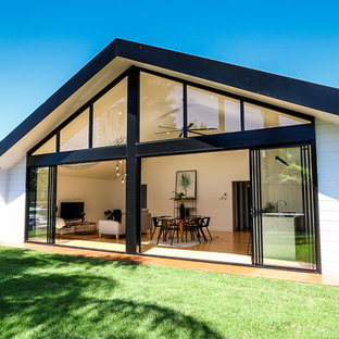 Photo of a large contemporary one-storey white house exterior in Brisbane with wood siding and a gable roof.