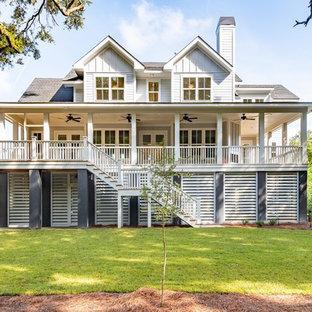 Foto de fachada de casa gris, costera, de tres plantas, con tejado a dos aguas y tejado de teja de madera