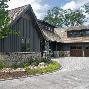 Пример оригинального дизайна: большой, двухэтажный, черный частный загородный дом в современном стиле с комбинированной облицовкой, вальмовой крышей и крышей из гибкой черепицы