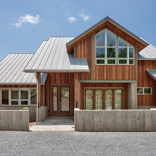 Example of a large trendy brown two-story wood house exterior design in Other with a hip roof and a metal roof