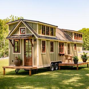 Ejemplo de fachada de casa verde, clásica, pequeña, de una planta, con revestimiento de madera, tejado a dos aguas y tejado de metal