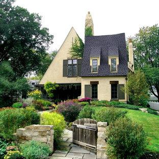Ejemplo de fachada de casa amarilla, clásica, grande, de dos plantas, con revestimiento de hormigón y tejado de teja de madera