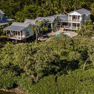 Diseño de fachada de casa blanca, ecléctica, grande, de dos plantas, con revestimiento de madera, tejado a dos aguas y tejado de metal