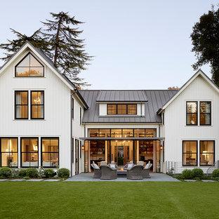 Esempio della facciata di una casa unifamiliare bianca country a due piani con tetto a capanna e copertura in metallo o lamiera