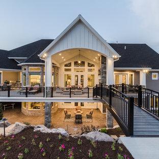 Cette image montre une façade de maison grise craftsman à un étage avec un revêtement en vinyle, un toit à deux pans et un toit en shingle.