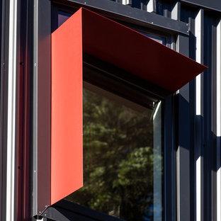 Foto della facciata di un appartamento piccolo multicolore a due piani con rivestimento in metallo, tetto a capanna e copertura in metallo o lamiera