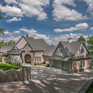 Imagen de fachada beige, ecléctica, extra grande, de dos plantas, con revestimiento de piedra y tejado a cuatro aguas