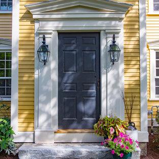 Diseño de fachada amarilla, de estilo de casa de campo, grande, de tres plantas, con revestimiento de madera