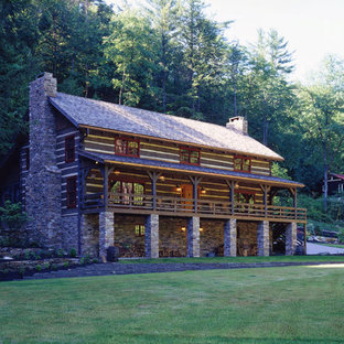 Example of a large mountain style brown three-story wood exterior home design in Other with a clipped gable roof
