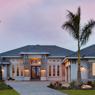 Diseño de fachada de casa gris, clásica renovada, extra grande, de una planta, con revestimientos combinados, tejado a cuatro aguas y tejado de teja de barro